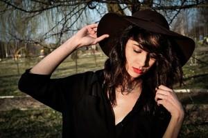 dziewczyna w czarnej tunice i brązowym kapeluszu