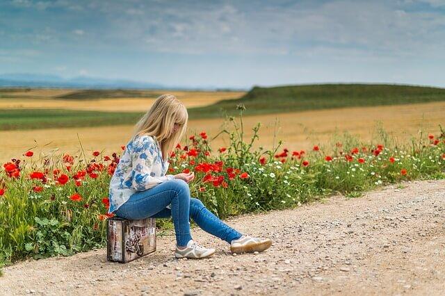 kobieta siedząca na walizce