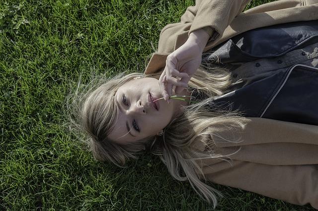 Dziewczyna w płaszczu leży na trawie
