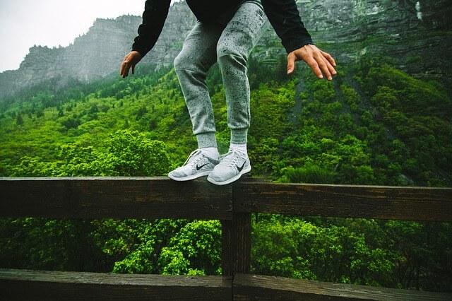 gość stoi na poręczy w butach Nike