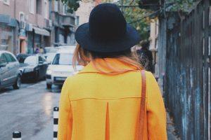 kobieta w żółtym płaszczu i kapeluszu